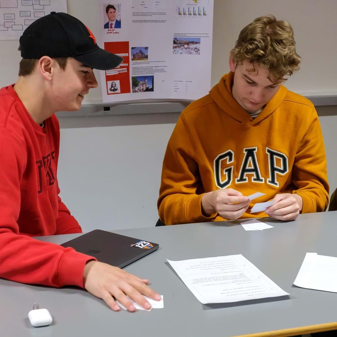 To drenge laver gruppearbejde og kigger på små sedler
