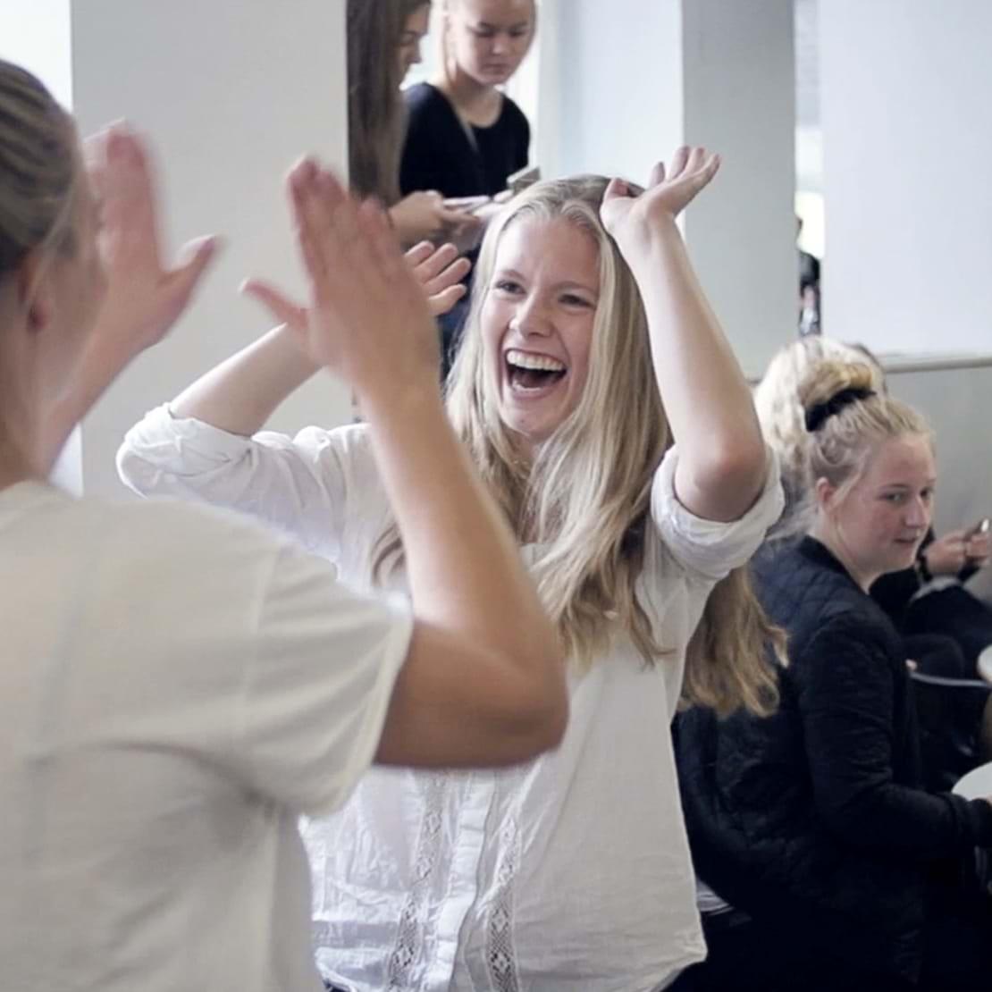 Elever som giver high-fives og har øl på bordet i forbindelse med fredagsbar