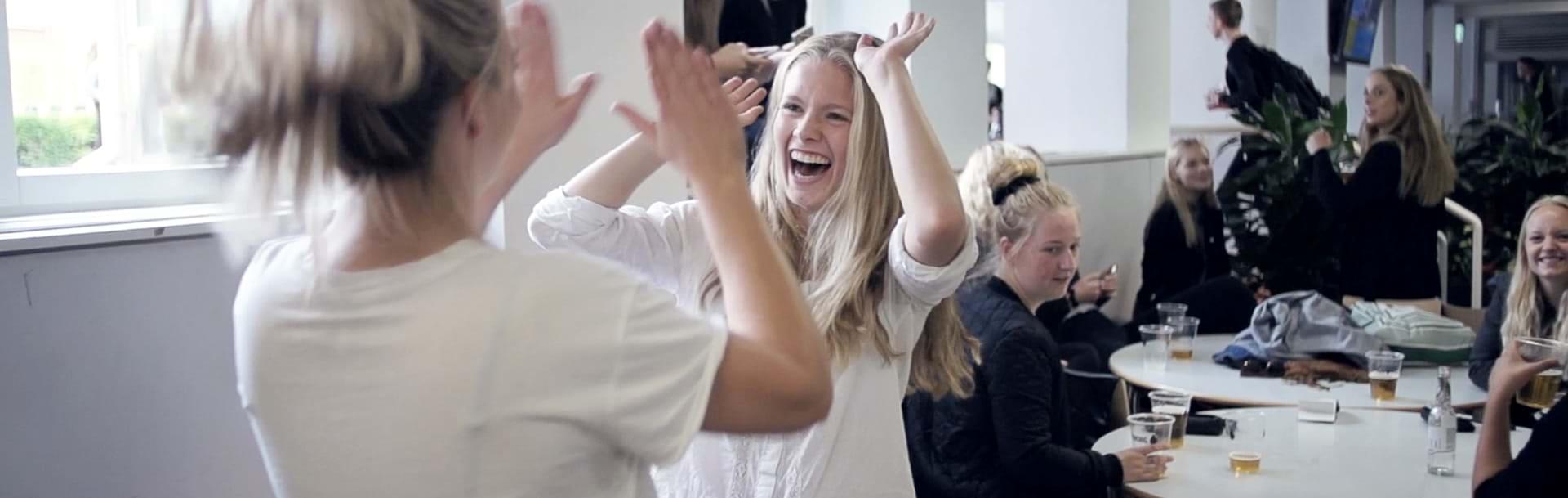 Elever som giver high-fives med øl på bordet til fredagsbar