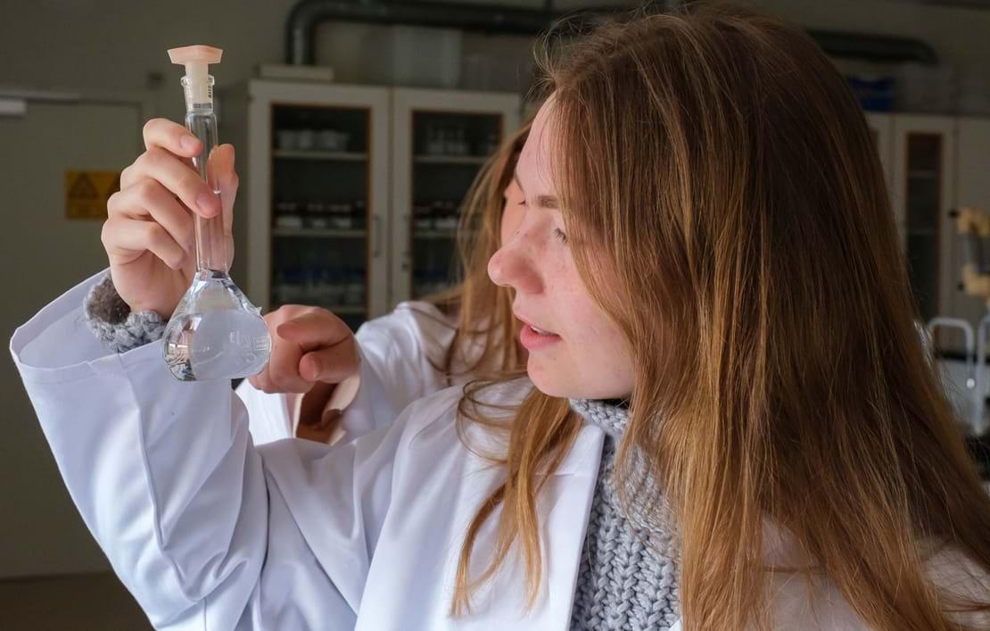 To piger nærstuderer kolbe i kemilokalet