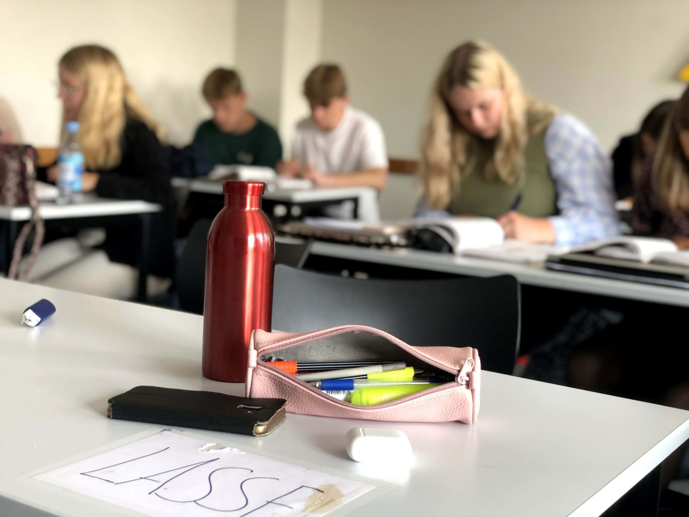 En tom plads ved et skrivebord med elever i baggrunden