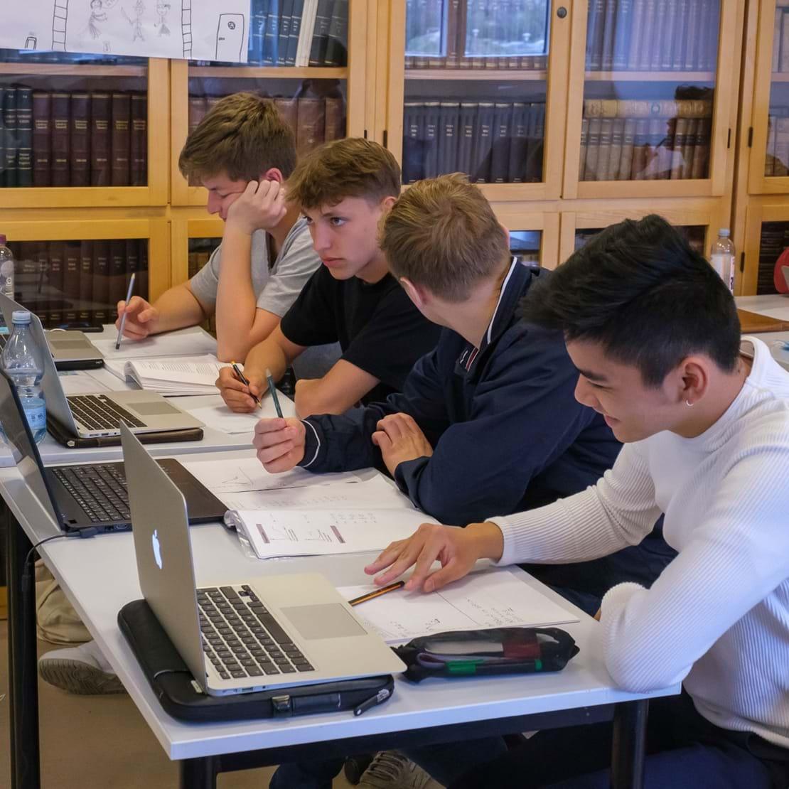 Fire HF elever sidder ved siden af hinanden i klasselokalet