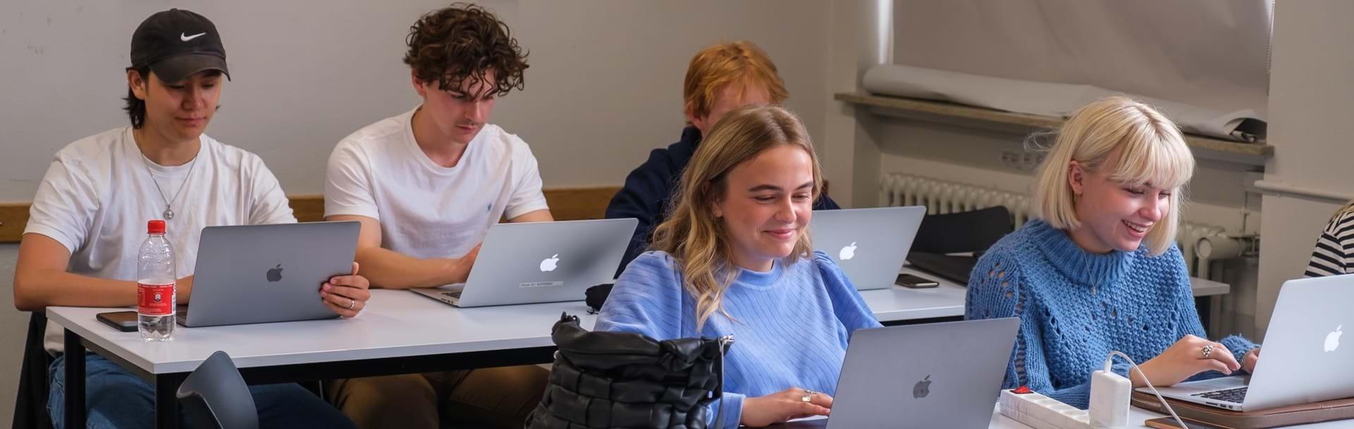 Elever arbejder på dere computere i klasselokalet