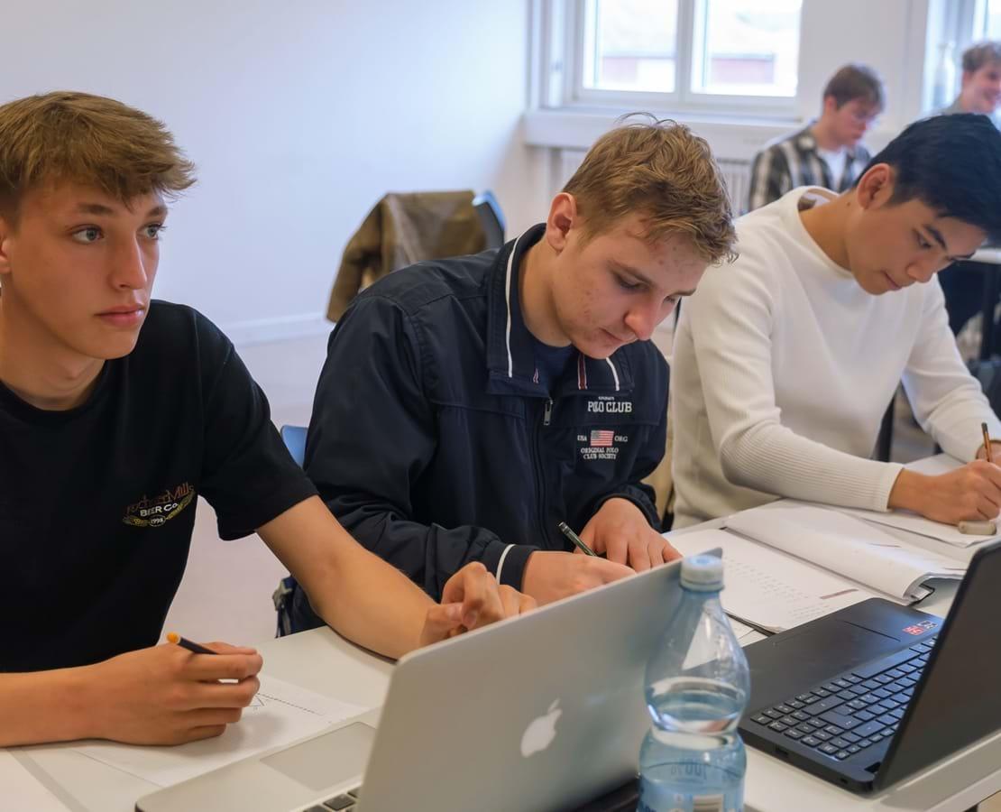 Tre drenge sidder ved siden af hinanden og laver opgaver i matematik