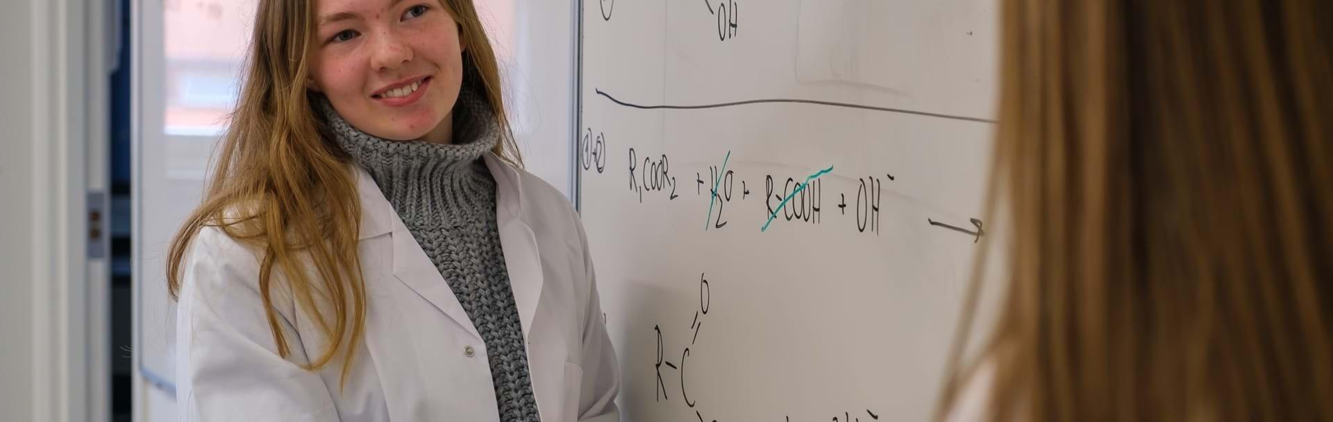 Pige i hvid kittel skriver formler på tavlen i kemilokale