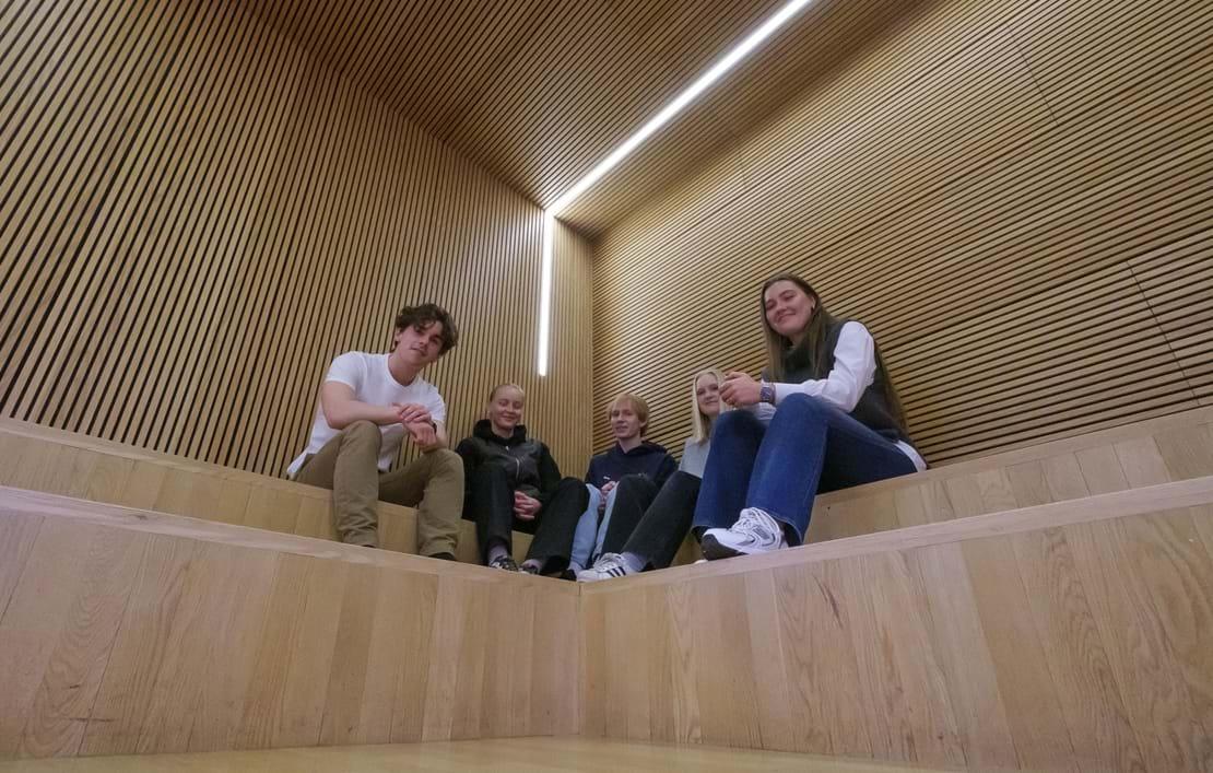 Fem elever sidder på indendørs trætrappe