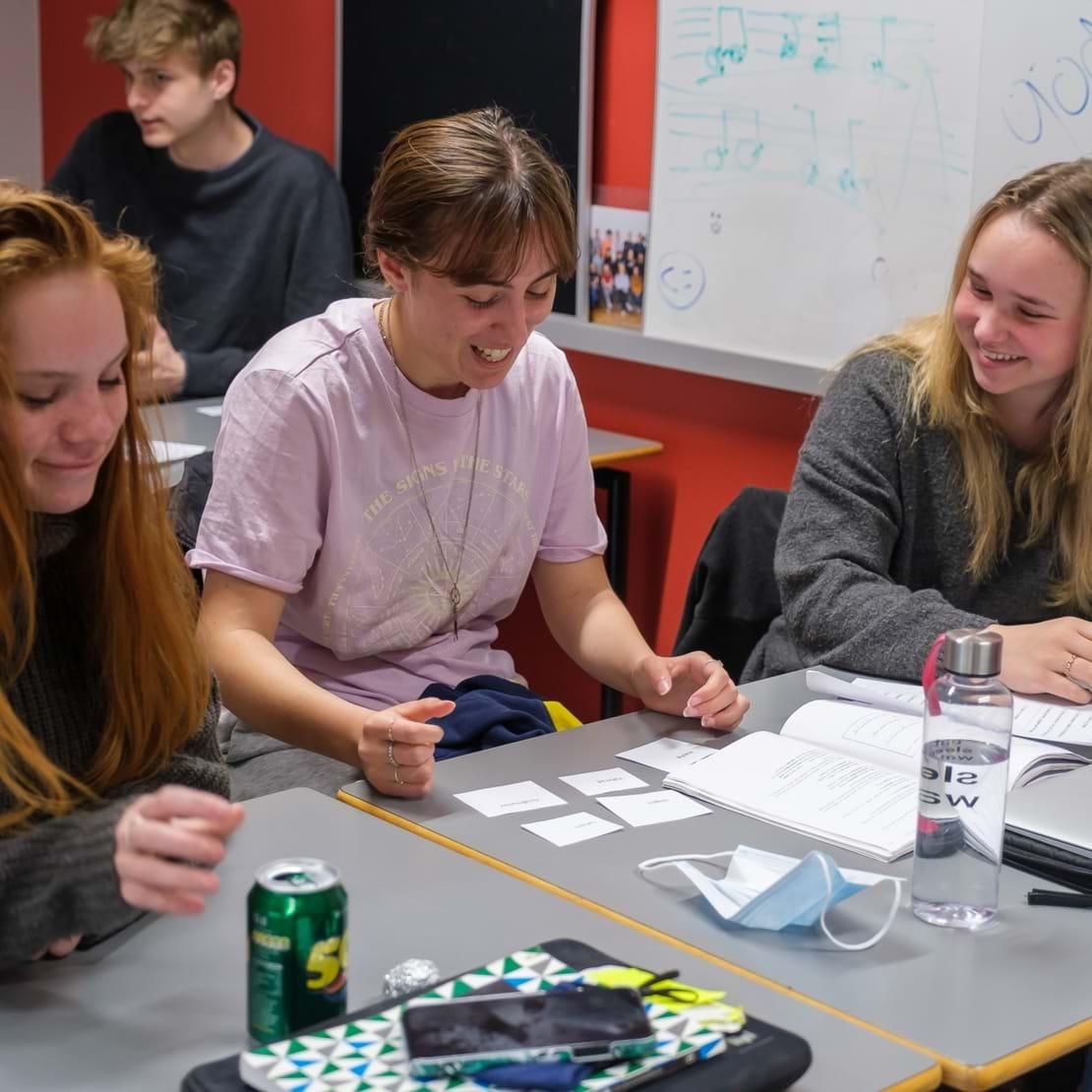 Tre piger laver gruppearbejde med små, hvide sedler