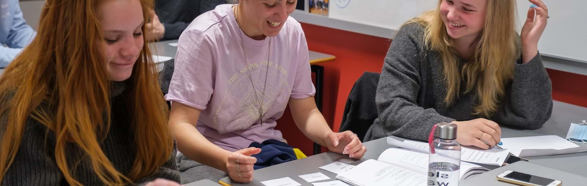 Tre piger sidder ved bord og laver gruppearbejde med små sedler