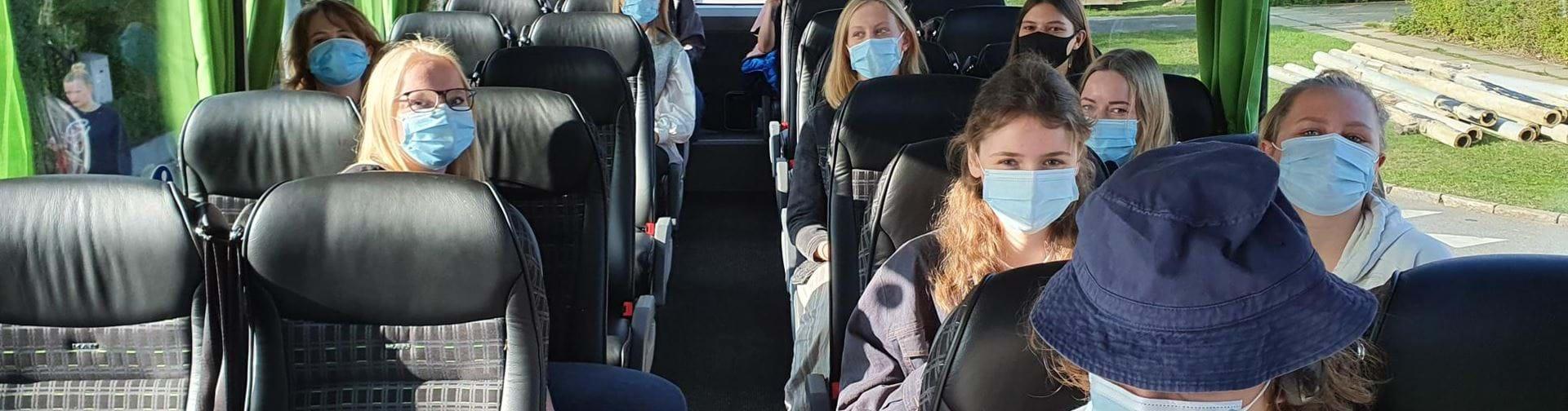 Elever med mundbind på i en bus på vej på tur