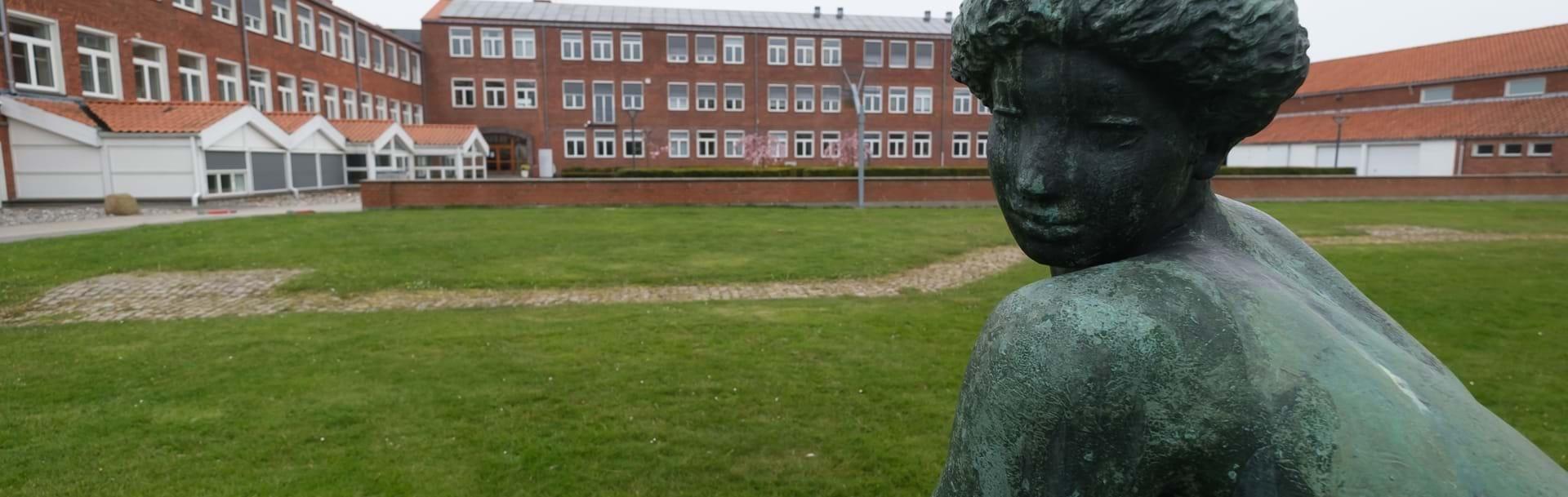 Nykøbing Katedralskoles bygninger set udefra med en statue i forgrunden