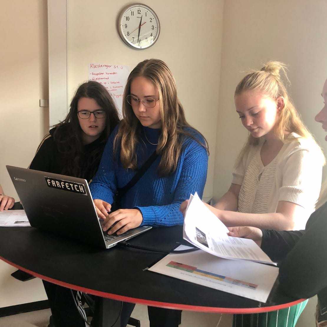Fem piger står samlet om én computer