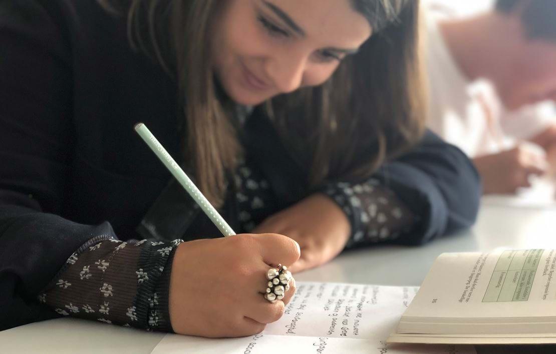Pige skriver noter i hånden