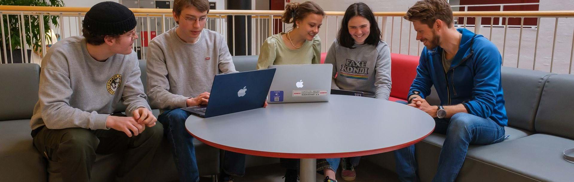 Fem unge hygger i sofa med deres computere i fællesarealet