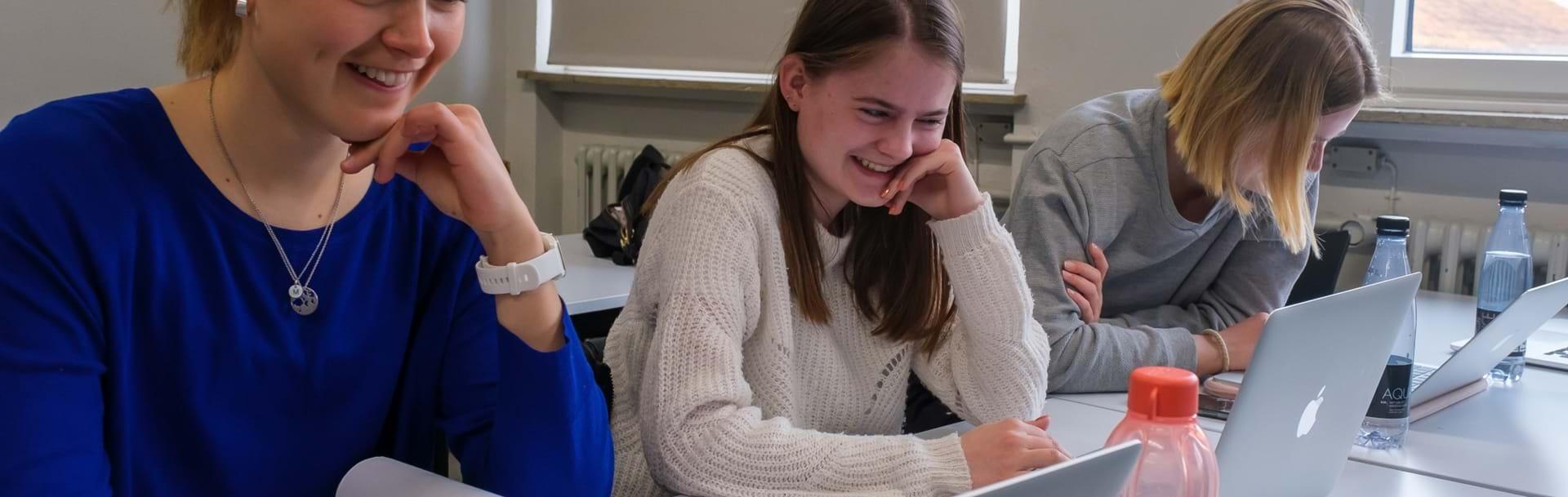 Tre piger sidder ved bord med deres computere