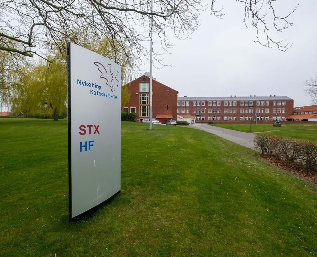 Skilt hvorpå der står Nykøbing Katedralskole STX og HF. I baggrunden skolens bygninger.
