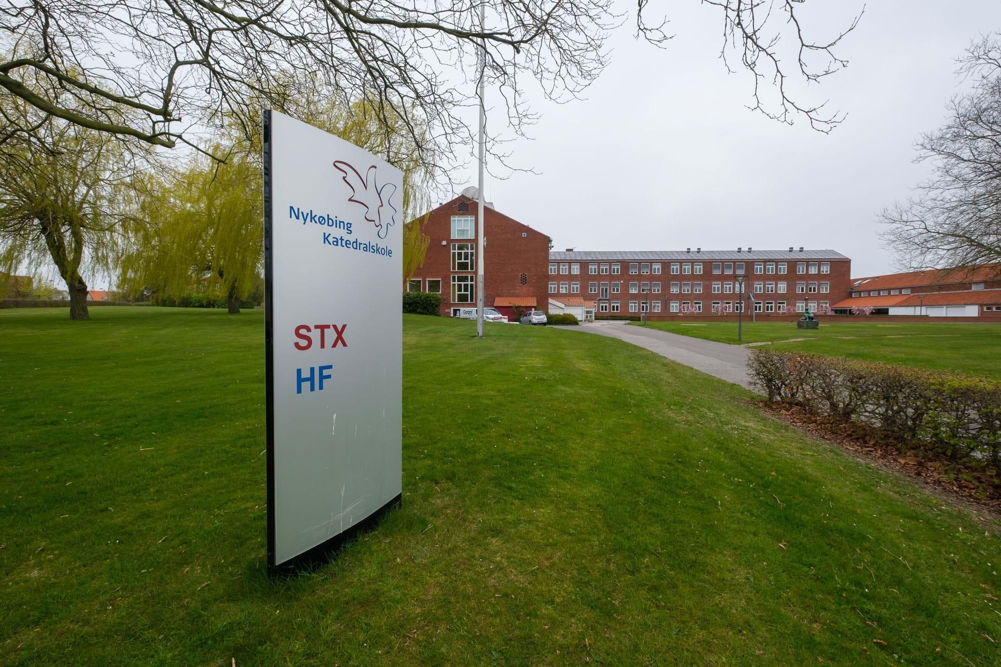Skilt i forgrunden med STX og HF og i baggrunden Nykøbing Katedralskole
