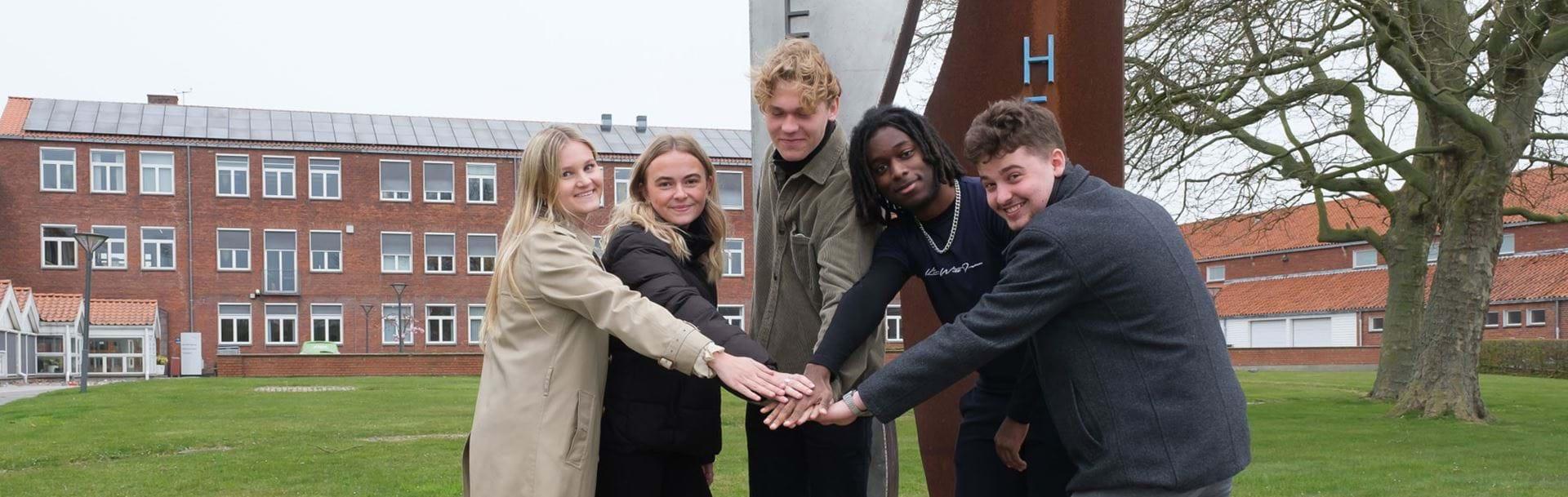 Fem unge står foran skilt ved skolen og lægger deres hænder over hinanden