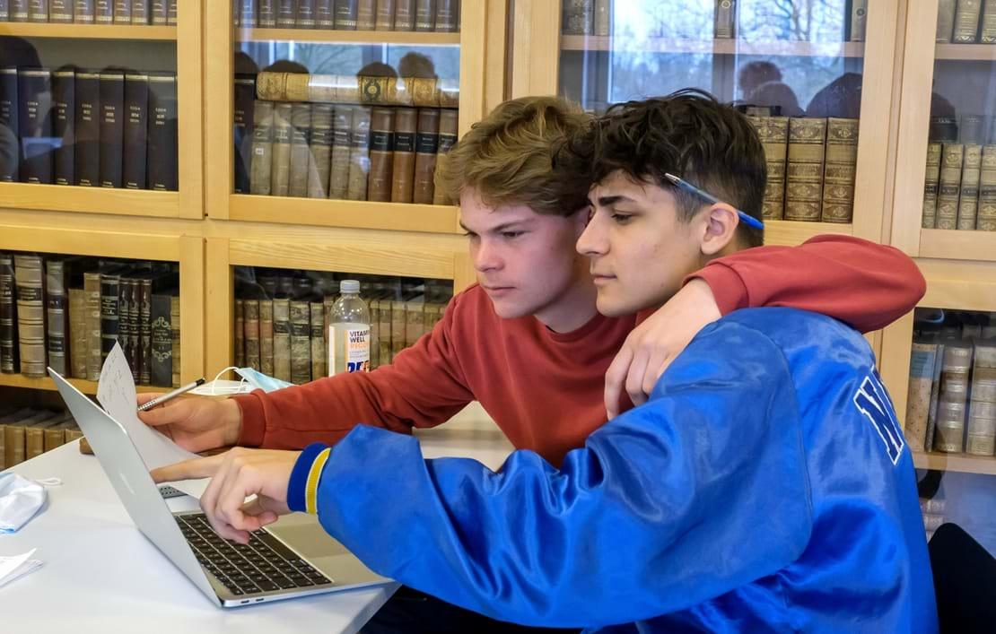 To drenge sidder og kigger på computerskærm foran skabe med bøger
