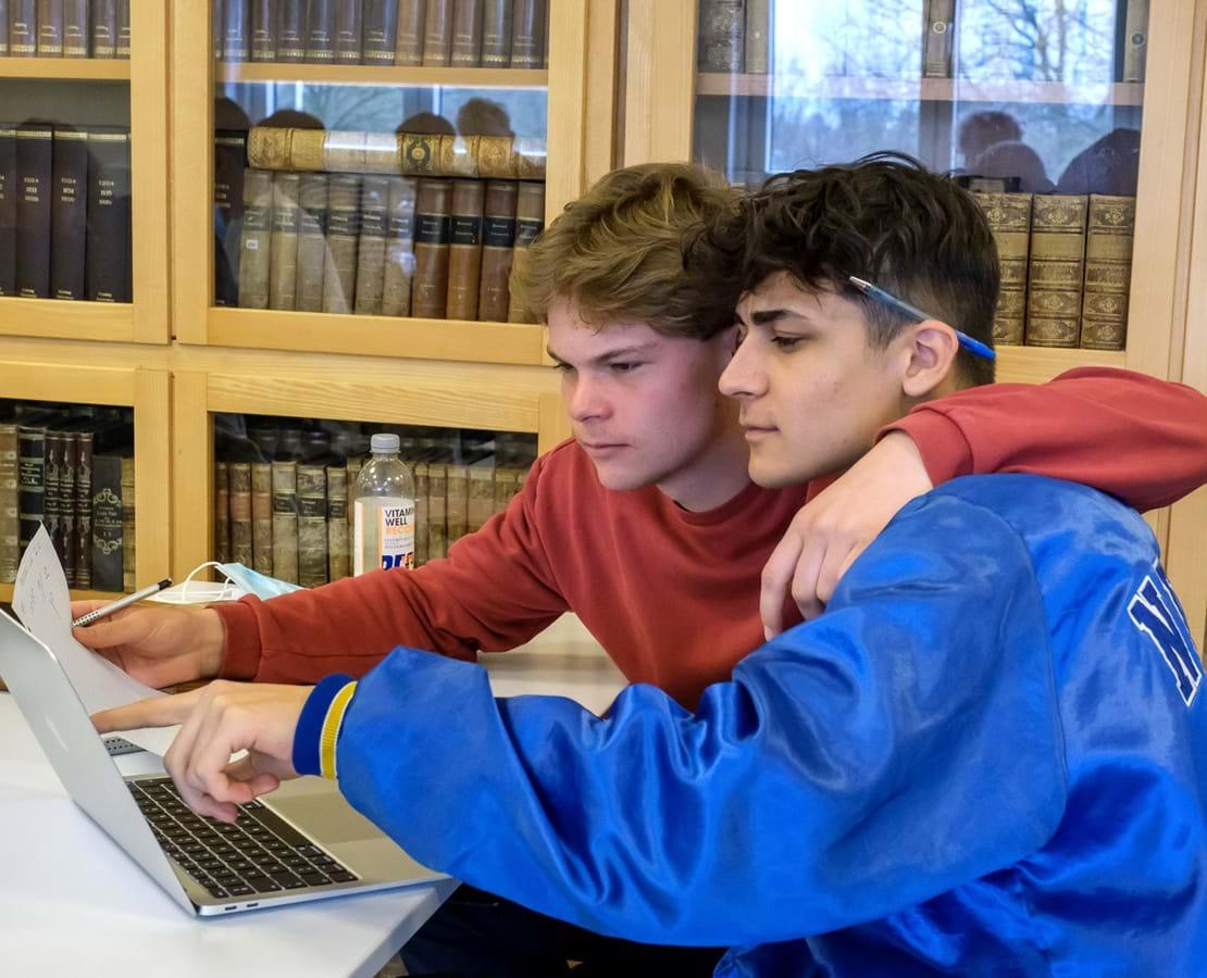 To drenge kigger på computerskærm. Den ene lægger armen om skuldrene på den anden