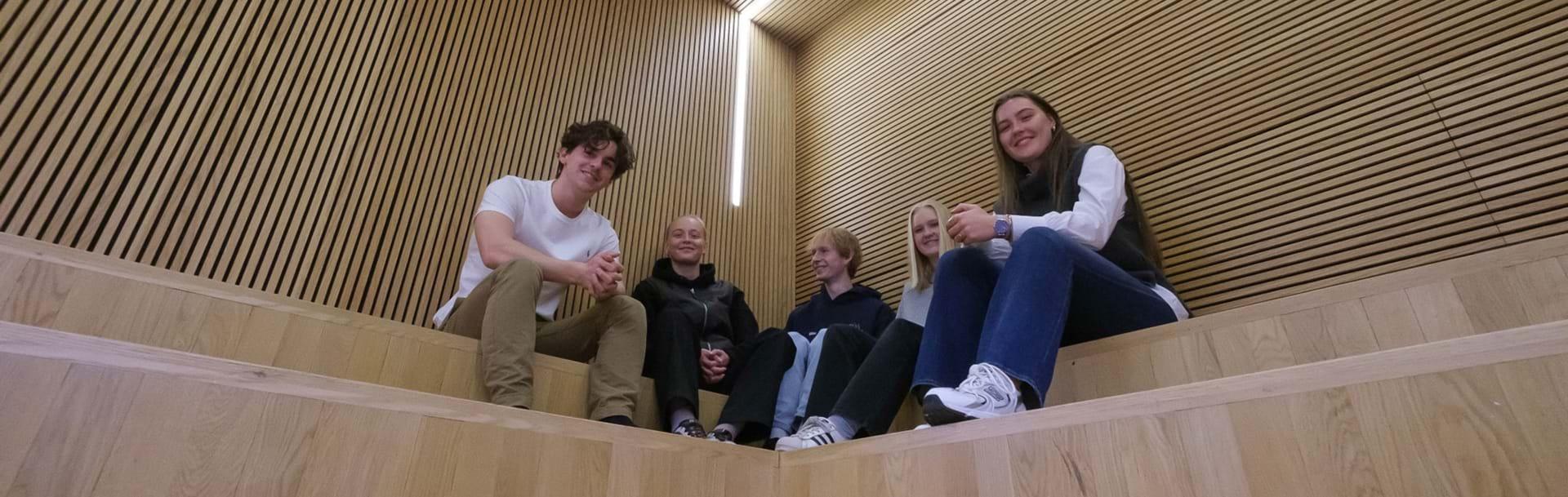 Fem elever sidder på indendørs trappe