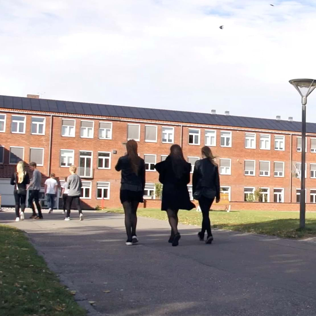 Tre elever på vej ind på skolen.